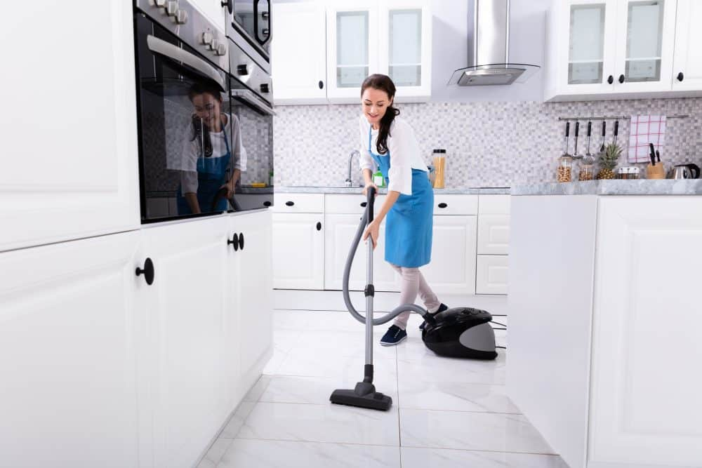 Young Female Janitor In Uniform Cleaning Kitchen Floor With Vacuum Floor