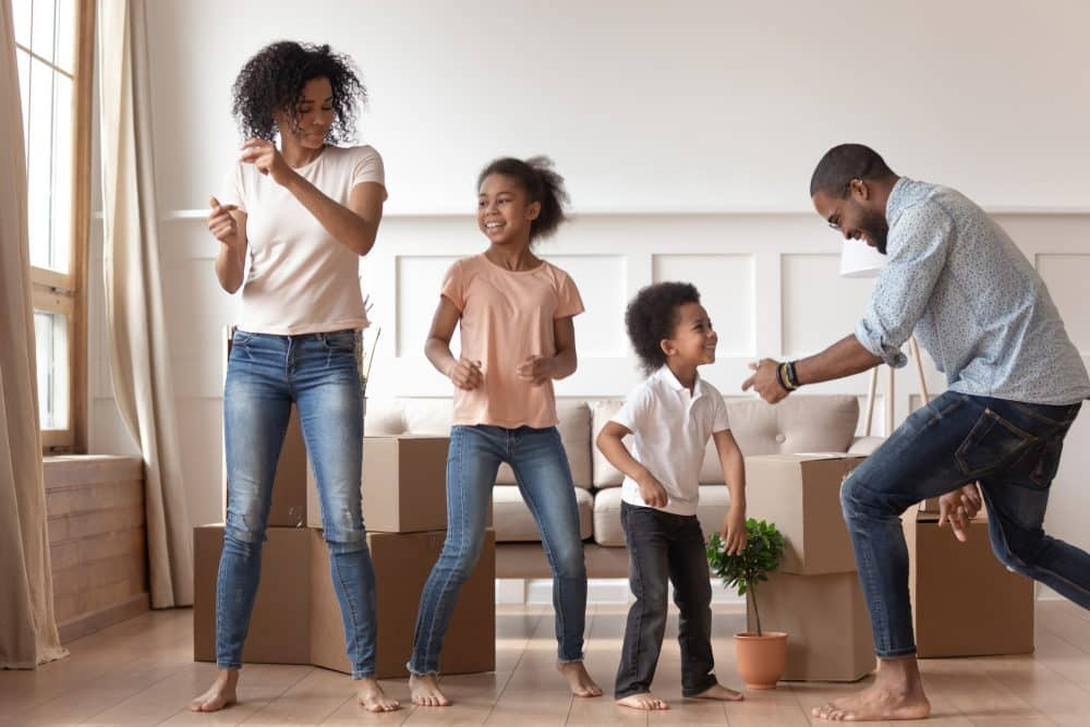 Active african couple and little children celebrating relocation moving day dancing feels happy stack of carton boxes on background as symbol of new home, delivery service, housing improvement concept