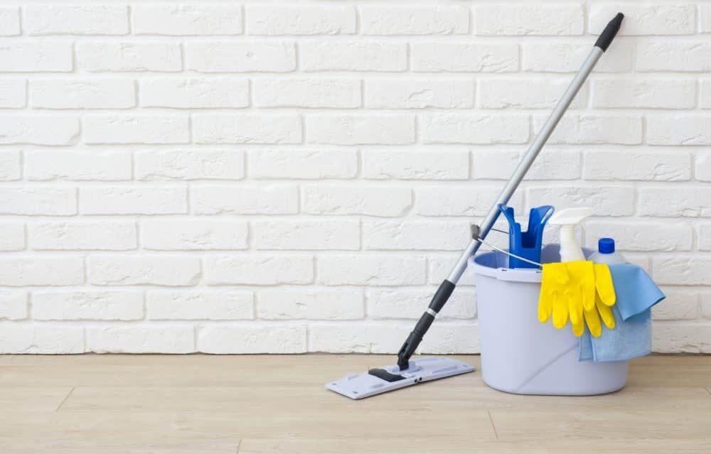Cleaning items on laminated floor in empty brick wall room