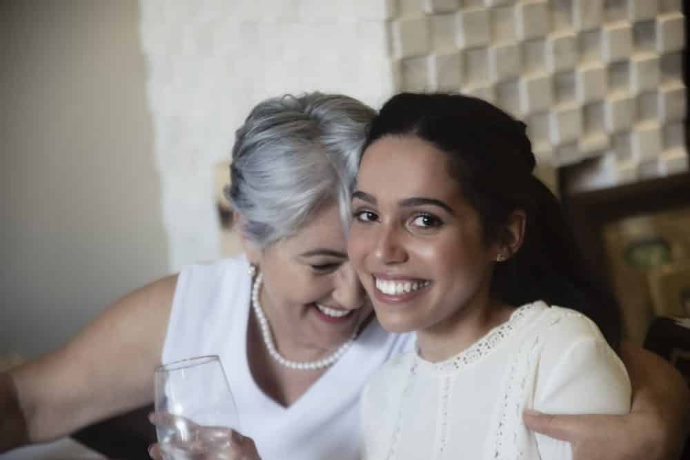 Senior woman embracing a teenage girl, as grandmother and granddaughter. Well dressed in white clothing, smiling, celebrating a special occasion.