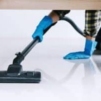 Housekeeping and housework cleaning concept, Happy young man in blue rubber gloves using a vacuum cleaner on floor at home.