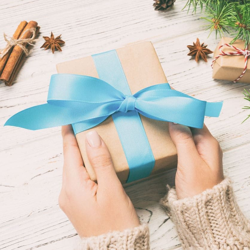 Female hands holding handmade present box in recycled paper on white wooden table background. christmas preparation concept, Gift wrapping background. Toned.