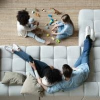 Above view parents sit on comfortable sofa while multi-ethnic daughters play on carpet using bricks set and dinosaur toys, new home and furniture, modern house, rented apartment family weekend concept