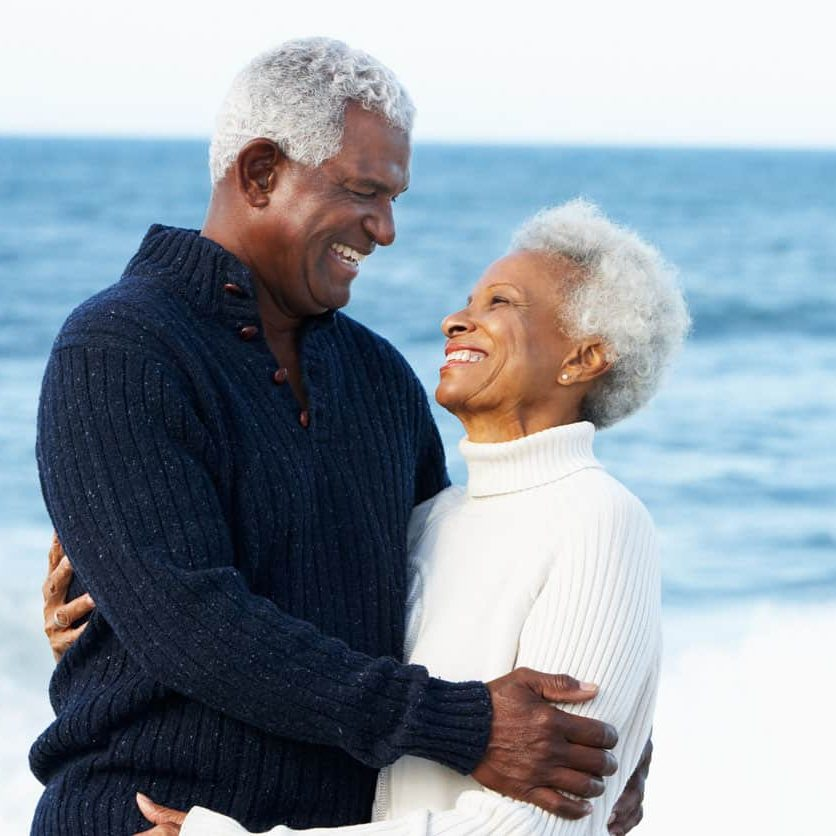 Romantic Senior Couple Hugging On Beach In Daytime Smiling At Each Other